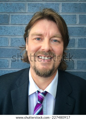 Image of a smiling business man in suit leaning against a wall