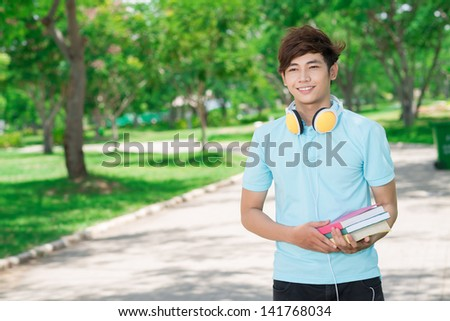 Image of a smiling guy with books in hands outside - stock photo