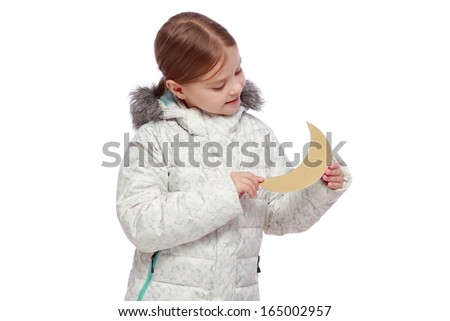 image of a smiling pretty little girl with a sweet smile in a warm winter coat holding a golden moon isolated on white on Christmas