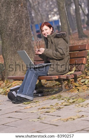 Image of a smiling redheaded girl holding her glasses in her hands and sitting on a bench with a laptop in her lap in an autumn park. - stock photo