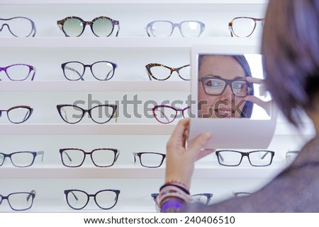 image of a smiling young woman reflected in a small mirror trying on glasses with a glasses exhibitor on background at optical store - focus on left eye