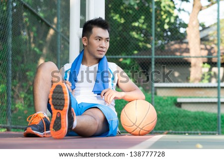 Image of a sweating basketball player sitting in the park - stock photo