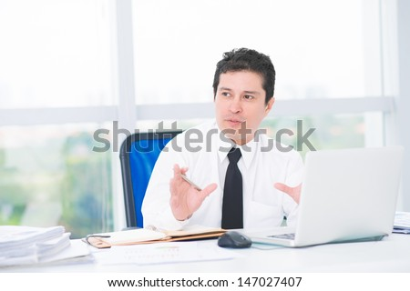 Image of a talking businessman at his workplace