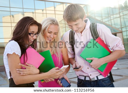 Image of a three young people looking at the cellphones