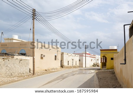Image of a village in Oman with power supply line - stock photo