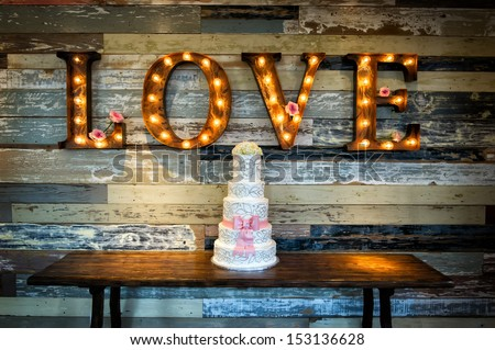 Image of a wedding cake with the word love as signage on a rustic background - stock photo