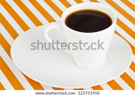 Image of a white mug with a dark coffee on a saucer on a stripe background - stock photo