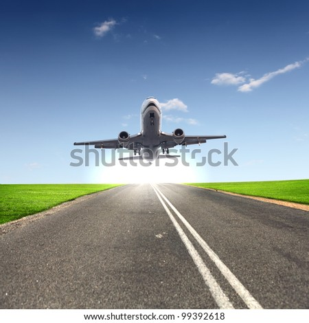 Image of a white passenger plane and blue sky with clouds