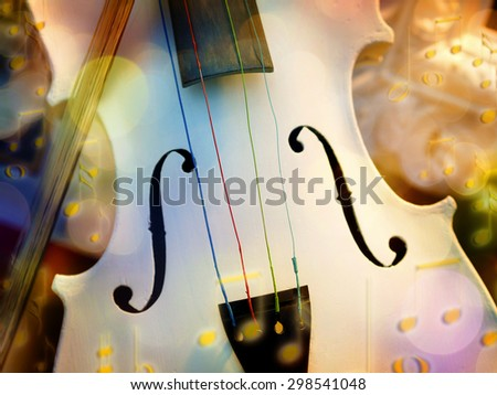 Image of a white violin with fiddlestick and bokeh