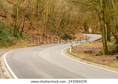 Image of a winding road through a forest - stock photo