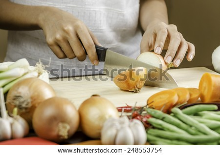 image of a woman cutting onion with vegetables around her - stock photo