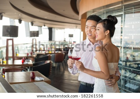 Image of a young adorable couple with red wine glasses at a restaurant  - stock photo