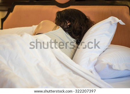 Image of a young adult woman sleeping or resting on the bed