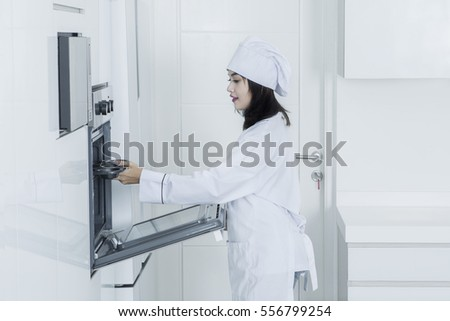 Image of a young Asian baker puts a baking tray into oven in the kitchen while wearing uniform