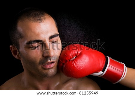 Image of a young boxer getting punched in the face over black background - stock photo