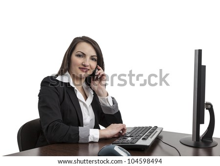 Image of a young brunette woman working on a computer and using a mobile phone , isolated against a white background.