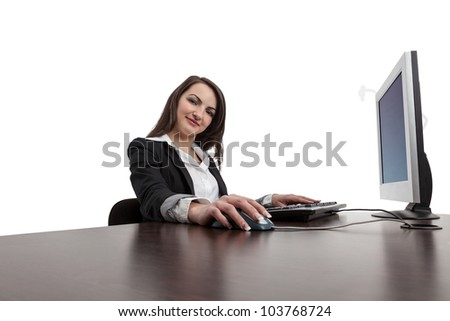 Image of a young brunette woman working on a computer while looking to the camera and smiling, isolated against a white background.