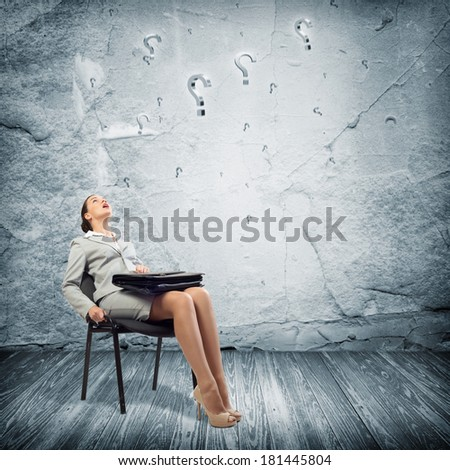image of a young business woman looking at the question marks
