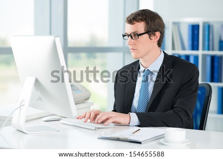 Image of a young businessman typing on computer at the office