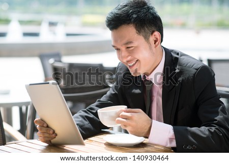 Image of a young businessman using his tablet during the lunch