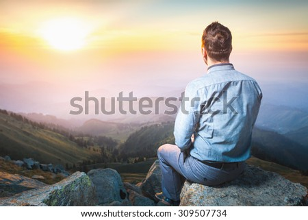 Image of a young businessman who sits on the top of the mountain and looks into the distance to the beautiful mountains, thinking about future plans - stock photo