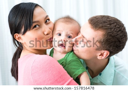 Image of a young cheerful family kissing his excited little baby on the foreground - stock photo