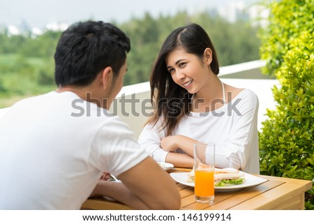 Image of a young couple having morning breakfast on the balcony of their apartment - stock photo