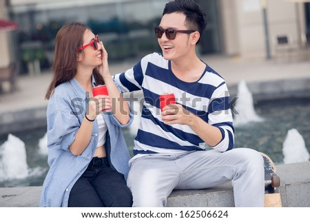Image of a young couple sitting with bottle of beverage and having fun outdoors - stock photo
