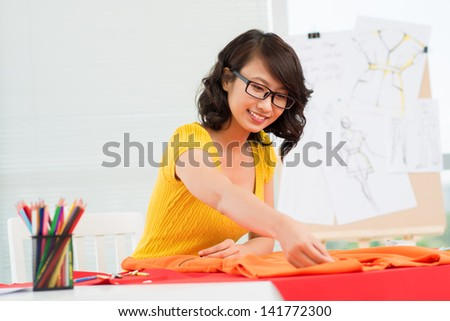Image of a young designer working in the atelier - stock photo