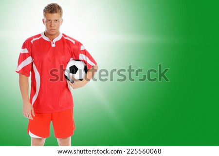 Image of a young football player with the ball in the red uniform - stock photo