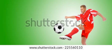 Image of a young football player with the ball in the red uniform. - stock photo