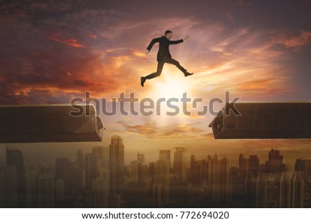 Image of a young male entrepreneur wearing formal suit while jumping gap on the bridge. Shot at sunset time