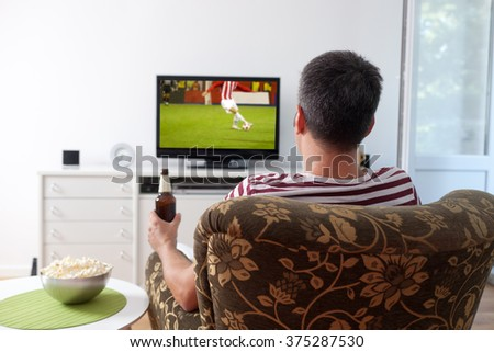 Image of a young man watching sports on TV - stock photo