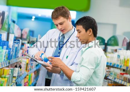 Image of a young medical intern helping the client to choose the treatment on the foreground