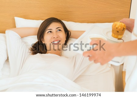 Image of a young woman lying in bed and waiting the breakfast - stock photo