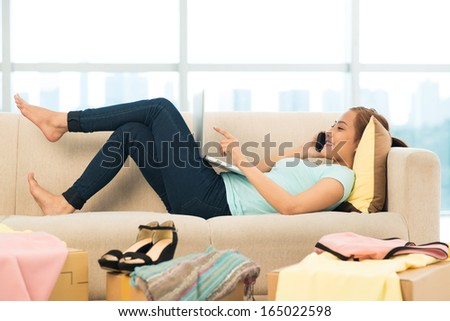 Image of a young woman lying on the sofa and talking by phone shopping online  - stock photo