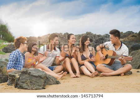 Image of a youngster singing to the guitar, his friends applauding - stock photo