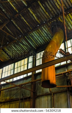 Image of abandoned warehouse ceiling with wires, metal beams and broken ventilation pipes.