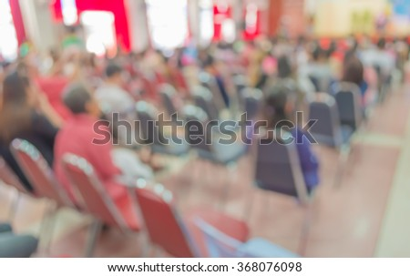 image of abstract blur people looking to kid 's show on stage at school , for background usage .