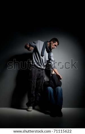 image of abuse and harassment.Young male is physically abusing and hurting other person in dark shadow room.