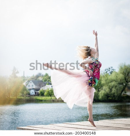 image of active life: beautiful blond young woman dancing in white skirt with falling sun light rays from sky at river or water lake on spring or summer nature green outdoors background copy space - stock photo