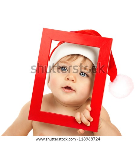 Image of adorable kid wearing funny Santa Claus hat, Christmas angel, nice little baby boy with blue eyes isolated on white background, curious child looking from red frame, New Year concept - stock photo