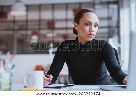 Image of african young woman working new business assignment. Female executive sitting at her desk using laptop and writing notes at office. - stock photo