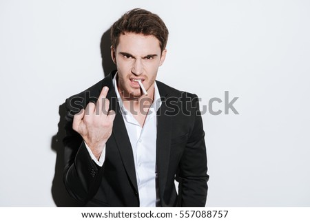 Image of aggressive businessman posing at studio and look at camera while holding cigarette and showing middle finger. Isolated over white background.