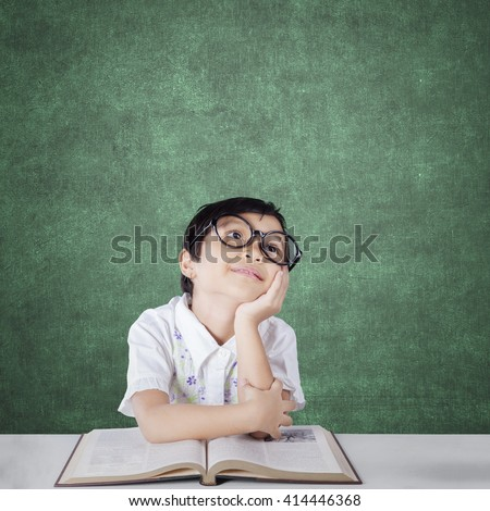 Image of an attractive elementary school student daydreaming in the classroom with a book on the table and wearing glasses - stock photo