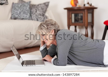 Image of an elderly happy woman lying on the floor and working on the laptop. - stock photo