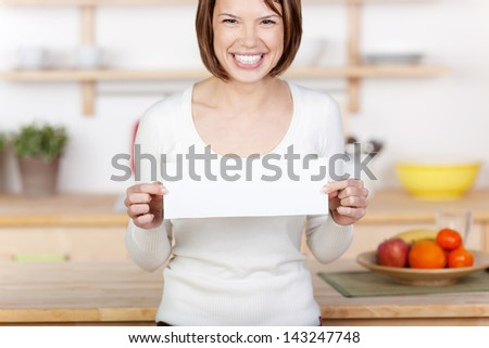 Image of an excited woman showing a sign in the kitchen. - stock photo