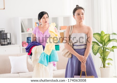 Image of an irritated mum conflicting with her teenage daughter at home  - stock photo