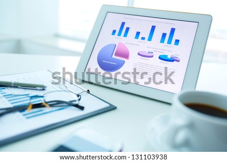 Image of an office workplace with document, touchpad and a cup of coffee - stock photo
