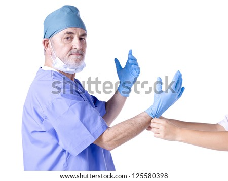 Image of an old doctor wearing medical gloves by the nurse - stock photo